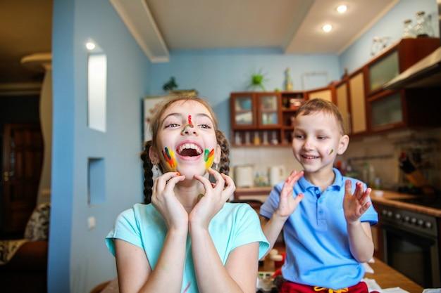 페인트 칠한 어린이 소년과 소녀가 부엌에서 집에서 웃고 바보짓을합니다.