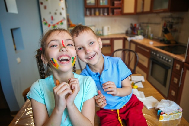 Smeared in paint children a boy and a girl fool around and laugh at home in the kitchen