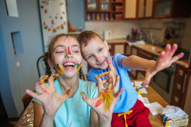 Smeared in paint children a boy and a girl fool around and laugh with their arms outstretched at home in the kitchen