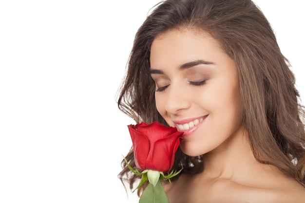 장미 냄새. 코 근처에 빨간 장미를 들고 흰색 배경에 격리된 동안 눈을 감고 있는 아름다운 젊은 여성