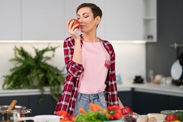 Нюхает свежее яблоко, держа его в руке, домохозяйка в клетчатой рубашке с короткой прической, пока