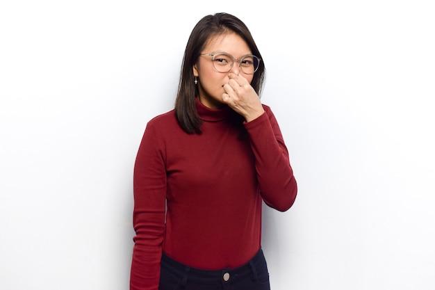 젊고 아름다운 아시아 여성이 빨간 셔츠를 입는 것의 악취와 역겨운 냄새