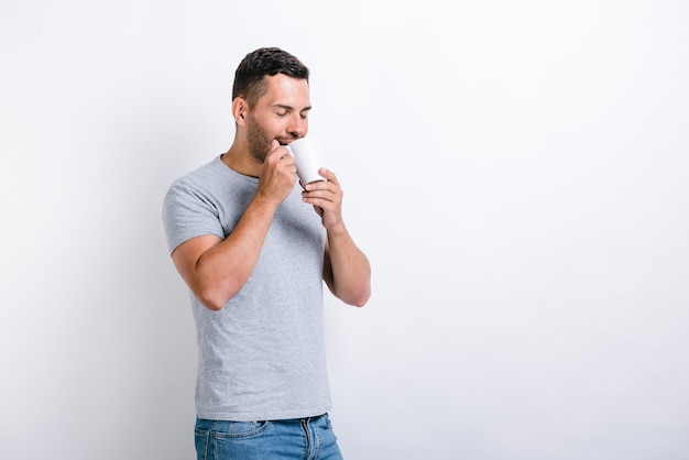 Smells great. waist up portrait view of the handsome man standing and sniffing aroma of the coffee from the cup. morning beverages concept. stock photo