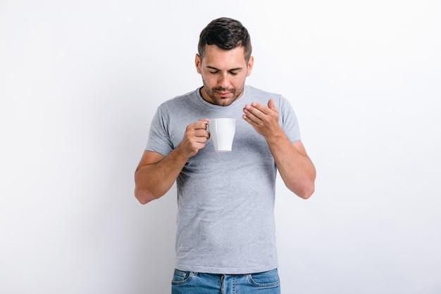 좋은 냄새가 난다. 잘 생긴 남자가 서서 컵에서 커피 향기를 맡는 모습을 허리 위로 올려 보세요. 아침 음료 개념입니다. 스톡 사진