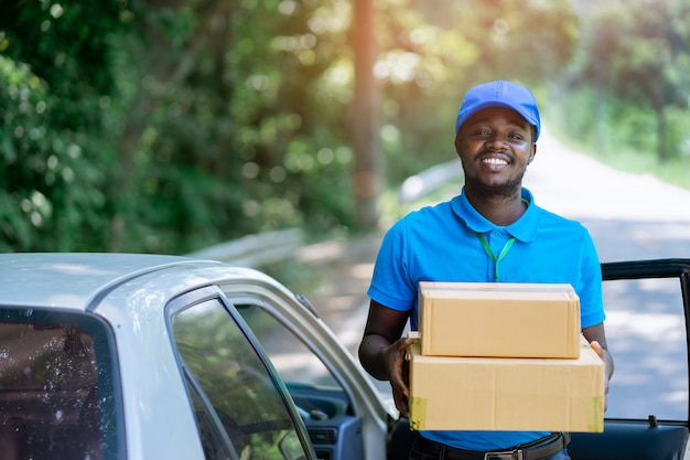 Smile african male postal delivery courier man in the car delivering package