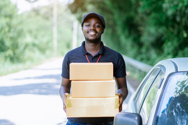 Smile african man postal delivery courier man in front of car delivering package