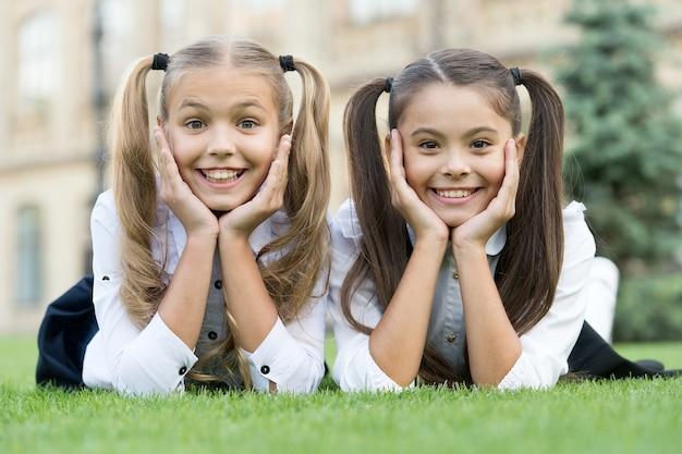 웃으면서 학교로 돌아가. 행복한 아이들은 푸른 잔디에 미소를 짓습니다. 치아 위생. 치아 건강. 소아 치과. 구강 의학. 귀여운 미소만 있으면 됩니다.