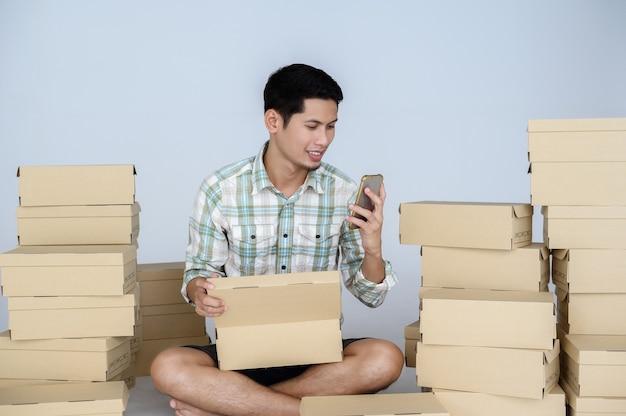 アジア人男性の笑顔と幸せそうな顔は、白い壁に小包が入った多くの箱の中にある彼のオンラインストアでスマートフォンを見ています。フリーランスのスタートアップとオンラインビジネスのホームオフィスの概念。