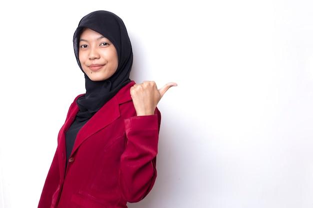 ヒジャーブを持つアジアの女性の笑顔と幸せそうな顔は、コンテンツの空のスペースを提示することを指しています。広告モデルの概念。
