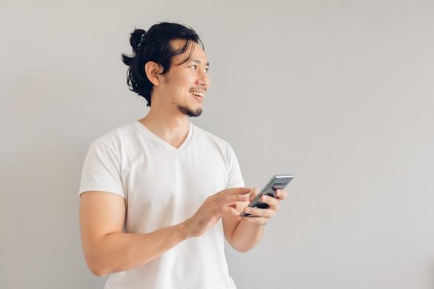 白のカジュアルなtシャツを着た笑顔と幸せの長い髪の男がスマートフォンを使用しています。