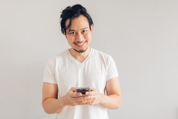 Улыбающийся и счастливый человек с длинными волосами в белой повседневной футболке использует смартфон.