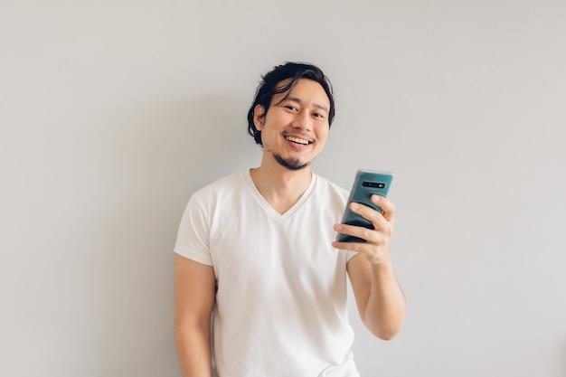 白いカジュアルなtシャツの笑顔と幸せな長い髪の男はスマートフォンを使用しています