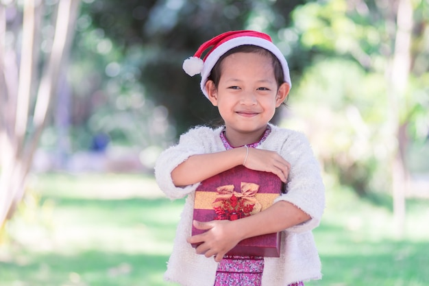Smile  asian child girl in santa red hat holding christmas gift box in hand. xmas concept.