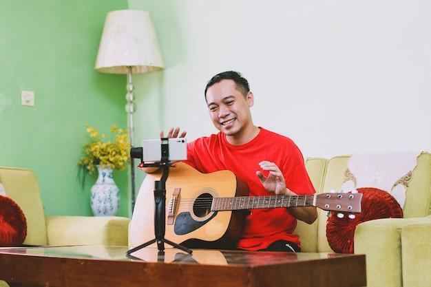 Улыбающийся азиатский мужчина держит гитару с жестом приветствия, глядя на смартфон