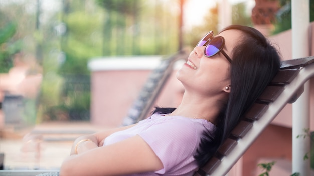 Smile asian woman lying on the wood chair and wearing sunglasses.