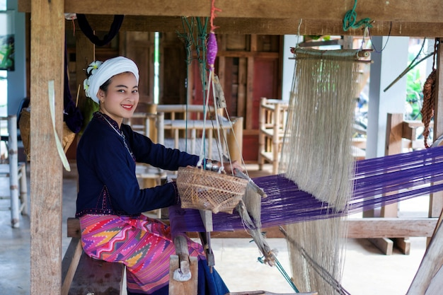 Smile asian woman in tai lue traditional dress (northern thailand culture) weaving fabric with old wooden machine