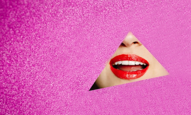 Smile of a beautiful girl with plump red lips peeks into a hole in pink glittering paper.fashion concept, beauty, make-up and cosmetics.