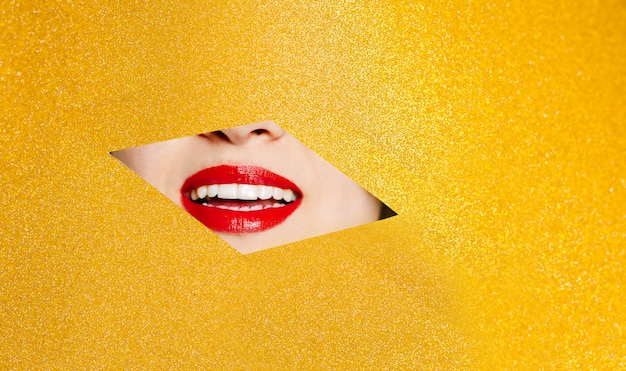The smile of a beautiful girl with plump red lips peeks into a hole in yellow glittering paper.fashion concept, beauty, make-up and cosmetics.