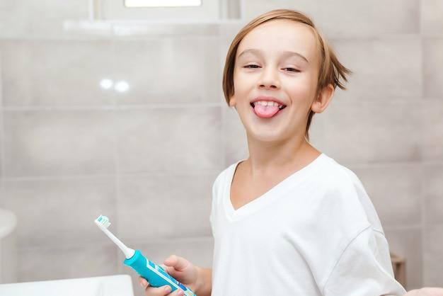 웃는 소년은 치아의 건강을 걱정합니다. 욕실에서 전기 브러시로 양치질하는 아이. 매일 치과 위생. 건강 관리, 어린 시절 및 치과 위생. 치아를 청소 하는 행복 한 소년.