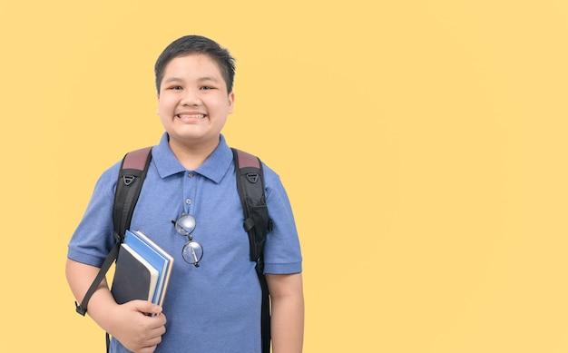 ランドセルを持って、黄色の背景に分離された本を持っている笑顔の男の子の学生、学校に戻るコンセプト。