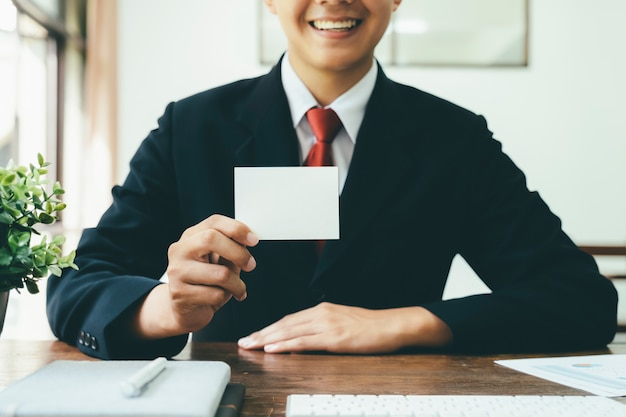 Smile businessman holding while blank business card