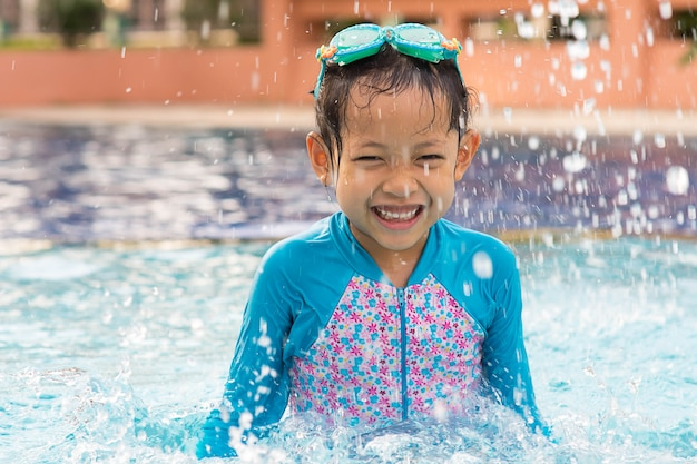 Smile child girl with goggles in swimming pool.