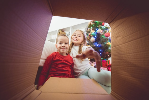 The smile children open the box near the christmas tree