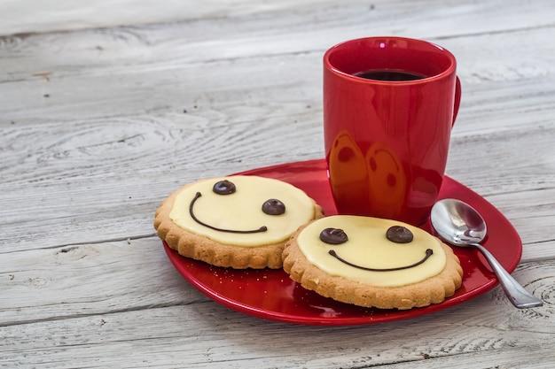 一杯のコーヒー、木製の壁、食べ物と赤いプレート上の笑顔のクッキー