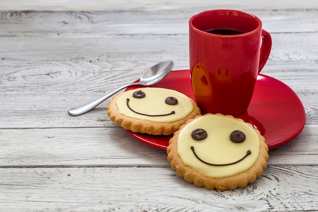 Smile cookies on a red plate with cup of coffee, wooden background, food