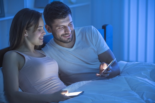 The smile couple phone in the bedroom. night time