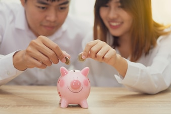Smile couple putting a coin into a pink piggy bank for buying house