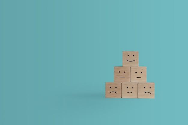 Улыбающееся лицо и значок тележки на деревянном кубе. оптимистичный человек или люди, чувствующие себя внутри, и рейтинг обслуживания при покупках, концепция удовлетворения в бизнесе.