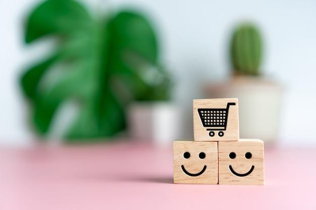 ウッドキューブの笑顔の顔とカートアイコン。楽観的な人、またはショッピングの際のサービス評価と満足度の概念。