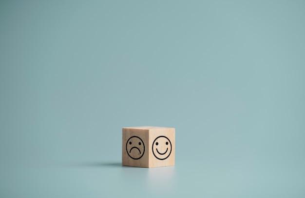 青い背景の上の木製の立方体ブロックの両面の笑顔と悲しみの顔のプリント画面
