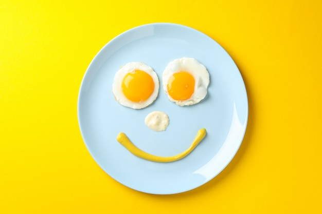 黄色の背景、上面に目玉焼きのプレートで作られた笑顔