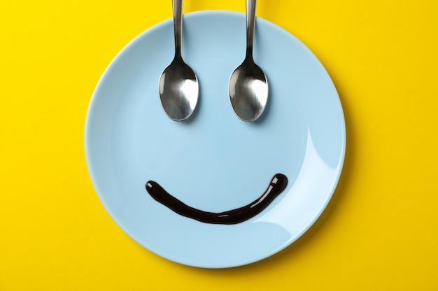 Smile face made of plate, chocolate syrup and spoons on yellow background, top view
