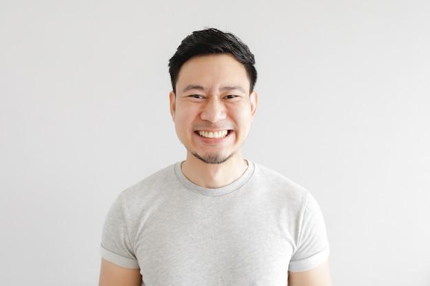 Улыбка счастливого азиатского мужчины в серой футболке на серой стене.