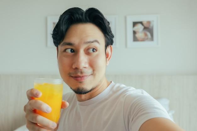 ホテルの部屋で夏のジュースを飲む幸せな男の笑顔