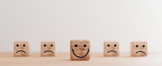 3dレンダリングによるカスタマーサービス評価と感情マインドセットの概念のための悲しみの顔の間の木製の立方体ブロック上の笑顔の顔の印刷画面。