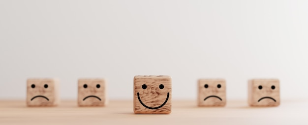 Smile face print screen on wooden cube block among sadness face for customer service evaluation and emotion mindset concept by 3d render.