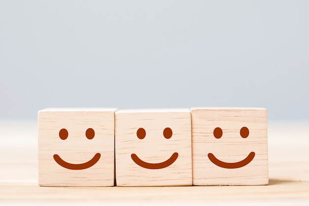 Smile face symbol on wooden cube blocks. emotion, service rating, ranking, customer review, satisfaction and feedback concept