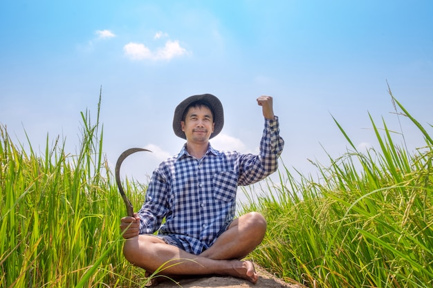 Smile farmer man wear hat sitting and hand up with beautiful rice paddy in rice field thailand