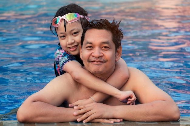 워터 파크 수영장에서 작은 딸과 함께 아버지 미소
