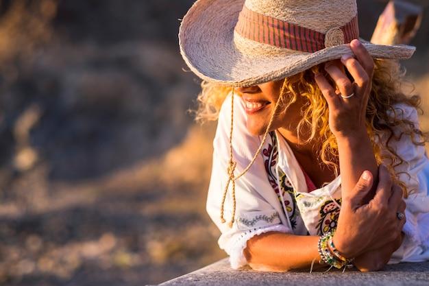 Улыбка модной кавказской женщины в ковбойской шляпе в солнечном отдыхе на свежем воздухе и расслабления - концепция счастливых людей с привлекательной блондинкой