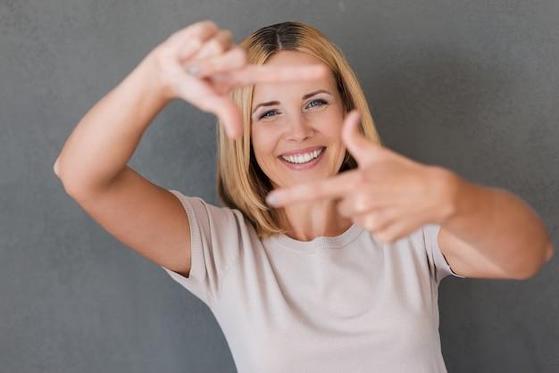 カメラに微笑んでください。カメラを見て、指のフレームを身振りで示す陽気な成熟した女性