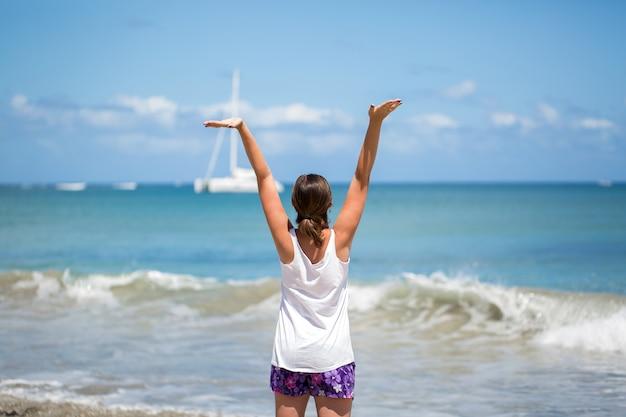 Улыбка свободы и счастья женщине на пляже. она наслаждается безмятежной океанской природой во время путешествий, отпуска, отдыха на природе.