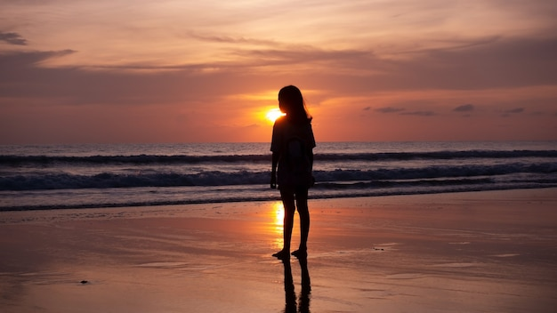 Smile freedom and happiness silhouette woman on beach summer travel vacation concept traveler asian teen girl standing on beach at sunset or sunrise in phuket thailand.
