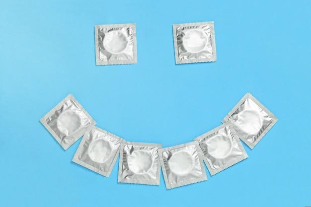파란색 배경에 포장된 콘돔에서 미소를 짓습니다.