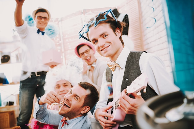 Smile gay guys in bow ties posing together on couch at party