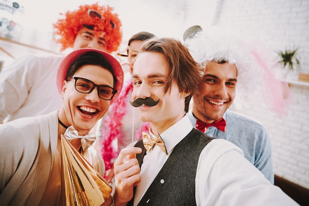 Smile gay guys in bow ties taking selfie on phone at party.